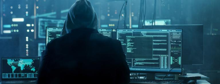 hacker in dimly lit room